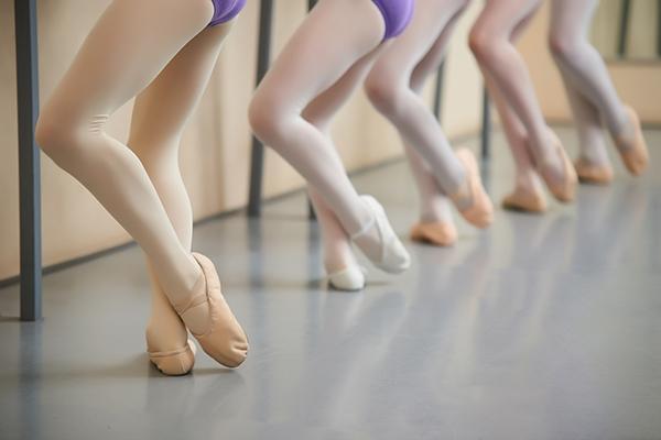 Ballerina training at hall, cropped image.